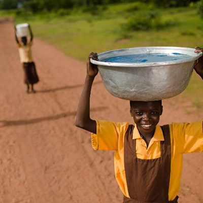 Boy carries water bowl on the head