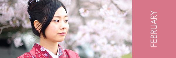 young Asian woman in kimono in front of cherry blossoms